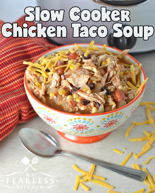 a bowl of chicken taco soup topped with shredded cheese with a slow cooker in the background