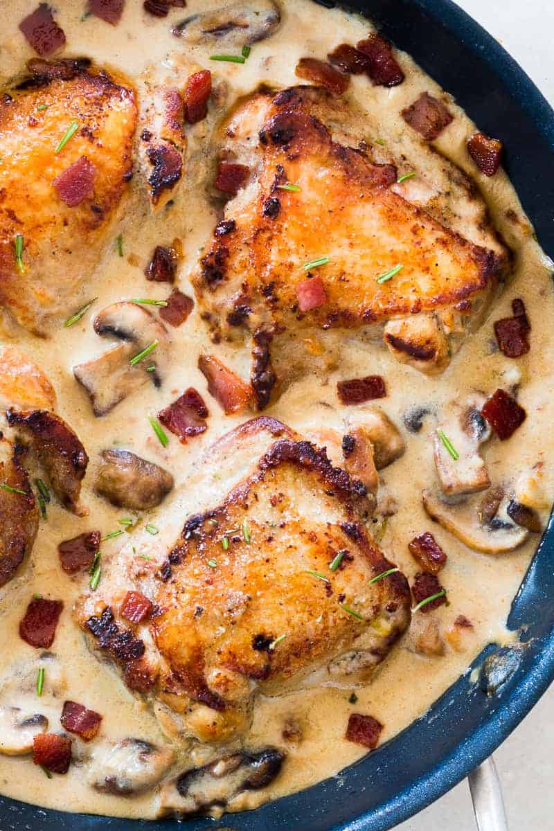 These creamy bacon rosemary mushroom chicken thighs are going to be your favorite weeknight comfort food. Chicken thighs are simmered in a lightened up alfredo like bacon sauce with mushrooms and rosemary. Serve it with pasta, or if you are looking for a low carb version, just add some steamed broccoli on the side.