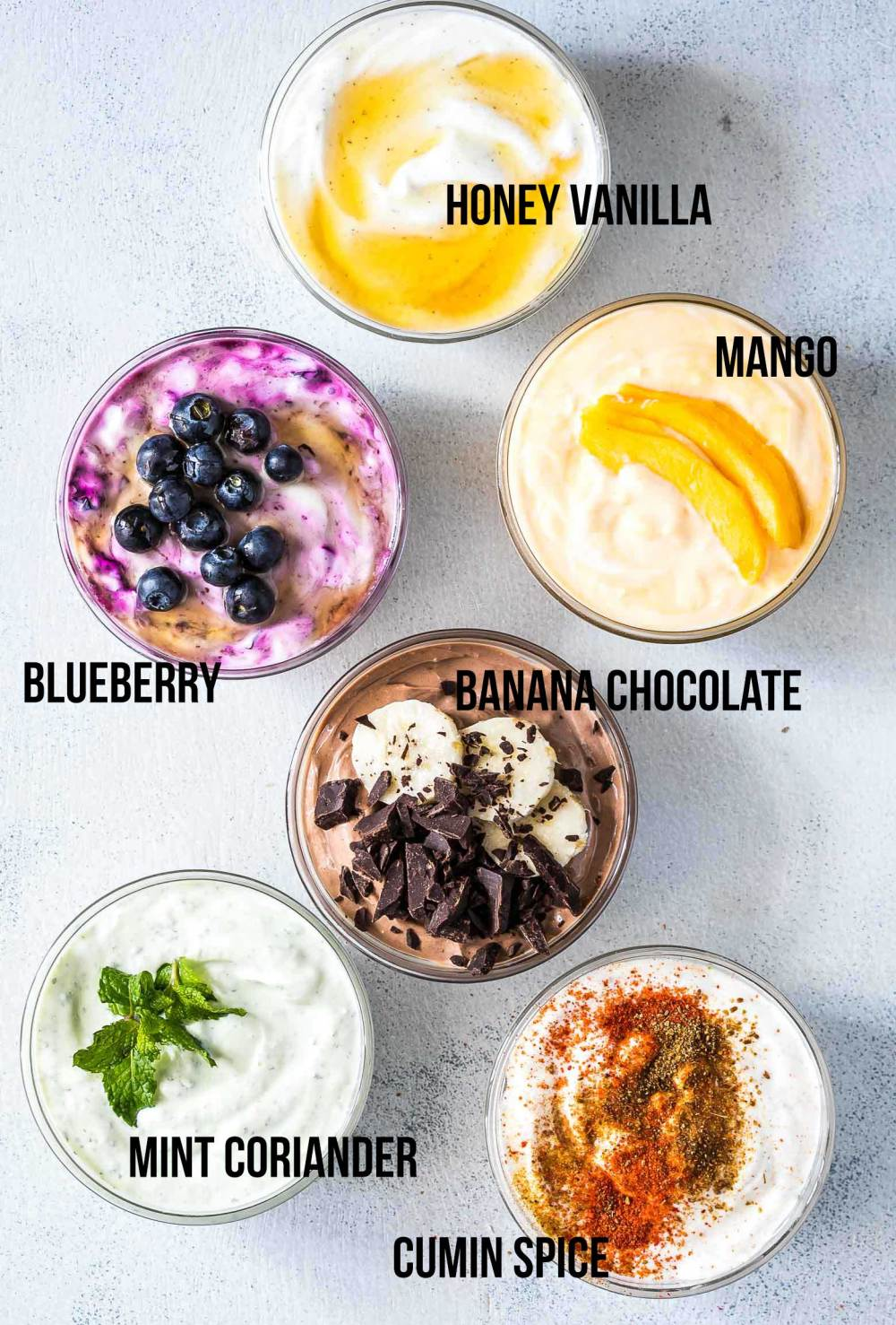 These six healthy Greek yogurt flavors are homemade and will become your breakfast buddies. Pick between honey vanilla, mango, blueberry, banana chocolate, mint coriander and cumin spice Greek yogurt or just make them all! No processed sugar, no fruit syrup or preservatives - just clean, healthy ingredients! You'll never go back to buying store bought flavored yogurt again.