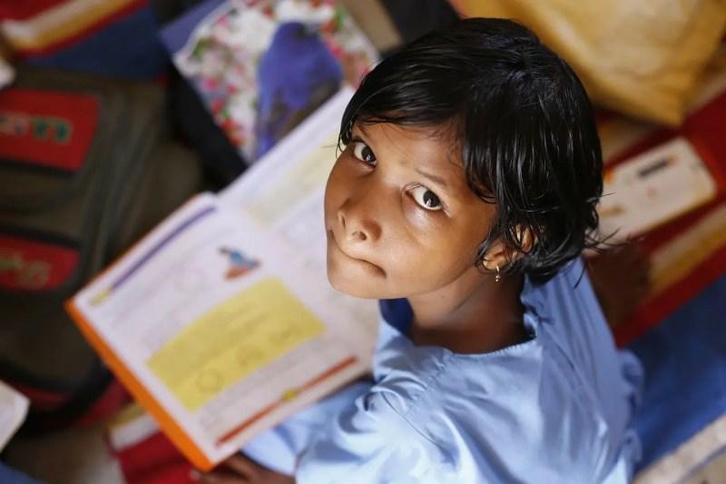 boy in school studying a book