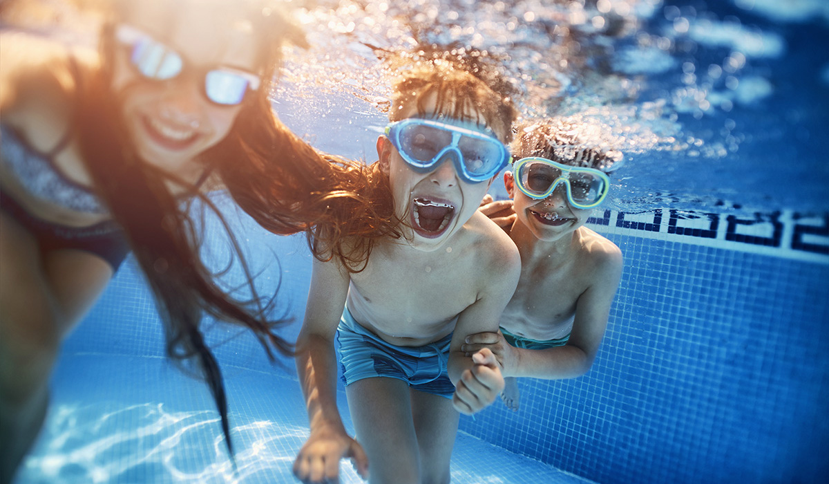 Kids playing under water in swimming pool