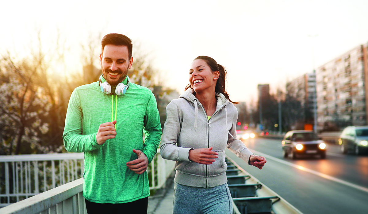 man and woman jogging outdoors in city