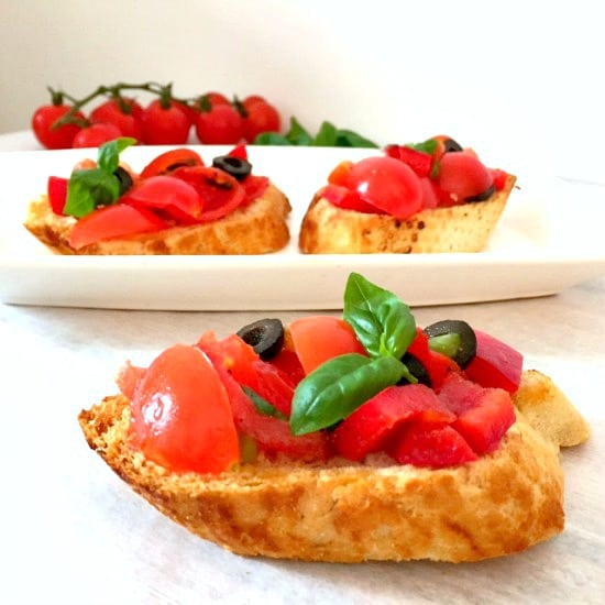 3 slices of Italian bruschetta topped with tomatoes, black olives and fresh basil