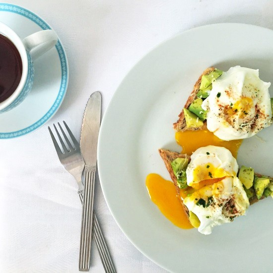 Overhead shot of a white plate with 2 poached eggs and avocado on toasts, a fork and knife next to it and a cup of tea