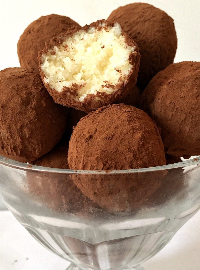 A bowl with coconut truffles dusted in cocoa powder with one truffle bitten into