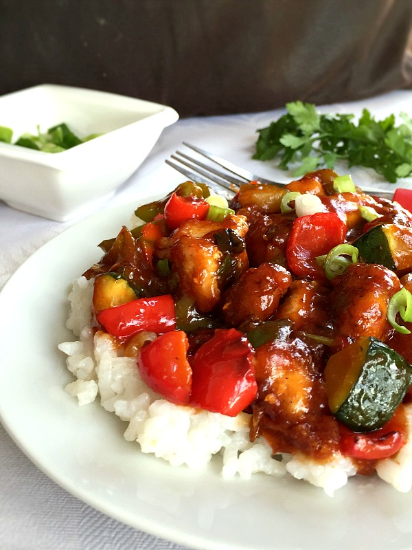A white plate of Sweet and sour chicken with vegetables