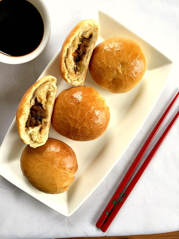 A white platter of 2 vegetarian dim sum buns and 2 halves of dim sum  with red chop sticks on the right side and a white bowl of soy sauce on the left hand side
