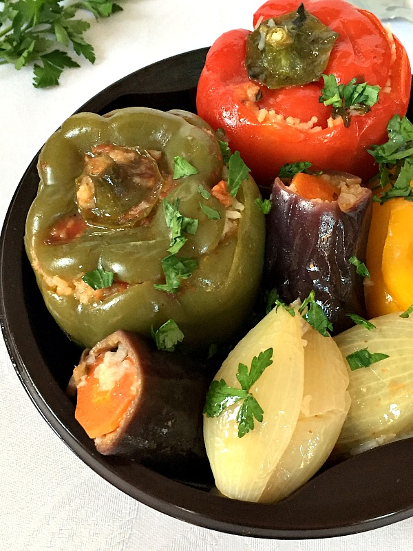 A black bowl of Vegetarian Dolma: stuffed red pepper, green pepper, 2 onions and 2 aubergines topped with chopped parsley