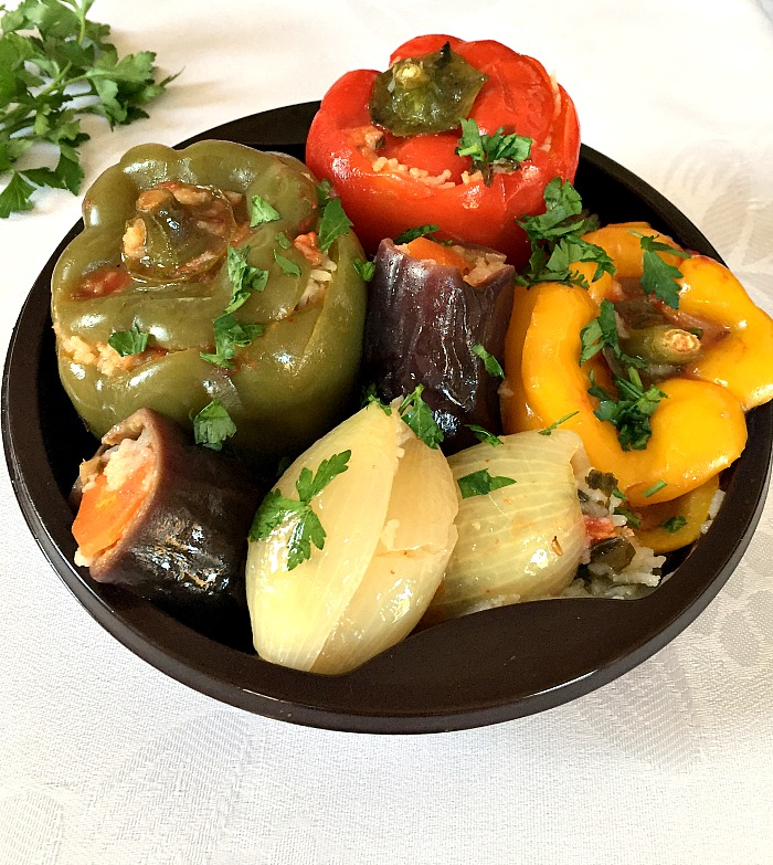A black plate of Middle Eastern vegetarian dolma: one stuffed red pepper, one stuffed yellow pepper, one stuffed green pepper, 2 stuffed onions and 2 stuffed eggplants (aubergines)