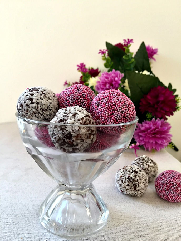 A glass bowl of chocolate brigadeiros, 3 brigadeiros on the table next to the bowl and flowers in the background