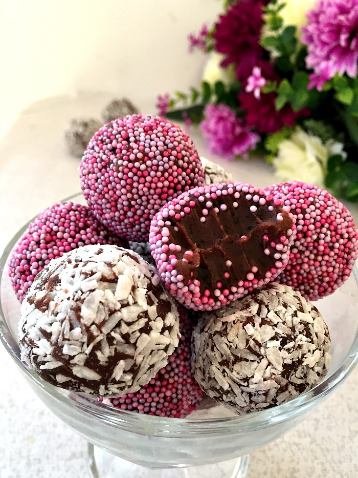 Close-up shot of a glass bowl of chocolate brigadeiros with flowers in the background