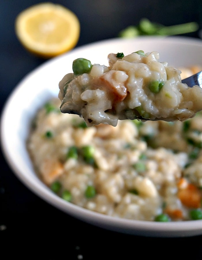 Creamy chicken risotto with peas on a fork with a white plate of more risotto in the background