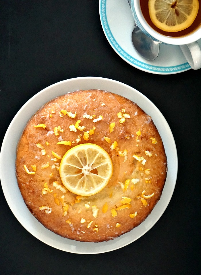 Overhead shot of a moist lemon drizzle cake on a white plate and a cup of tea with a lemon slice