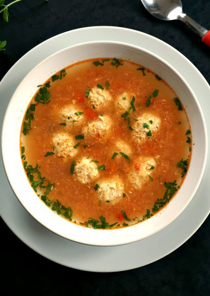 Overhead photo of a white bowl of meatball soup garnished with lots of fresh parsley