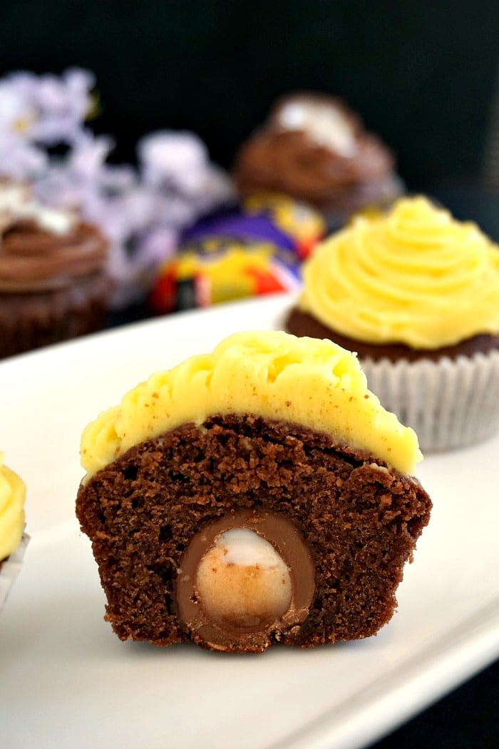 Cadbury creme egg cupcakes halved to reveal the hidden creme egg. With a delicious lemon frosting on top, these cupcakes are perfect for Easter.