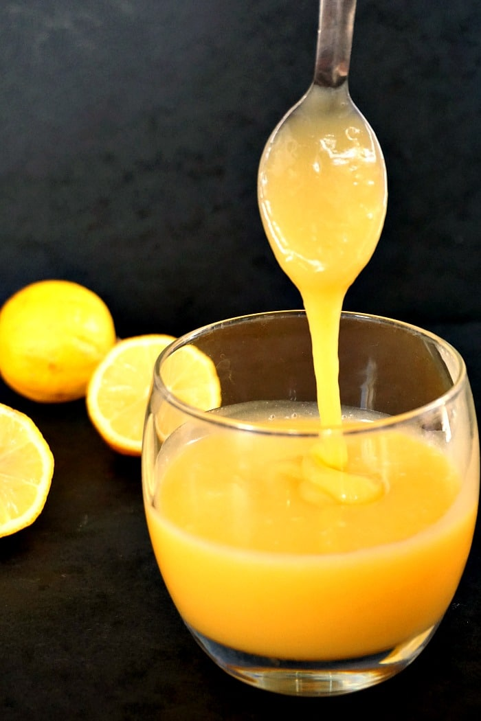 Spoon drizzling lemon curd into a glass, 1 whole lemon and 2 half lemons in the background