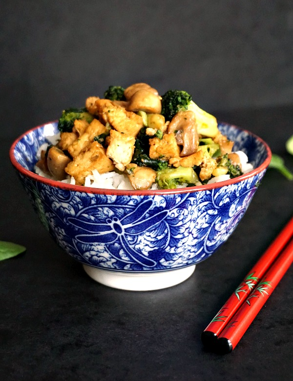 A blue and white bowl of broccoli tofu stir fry with basmati rice and red chopsticks next to it