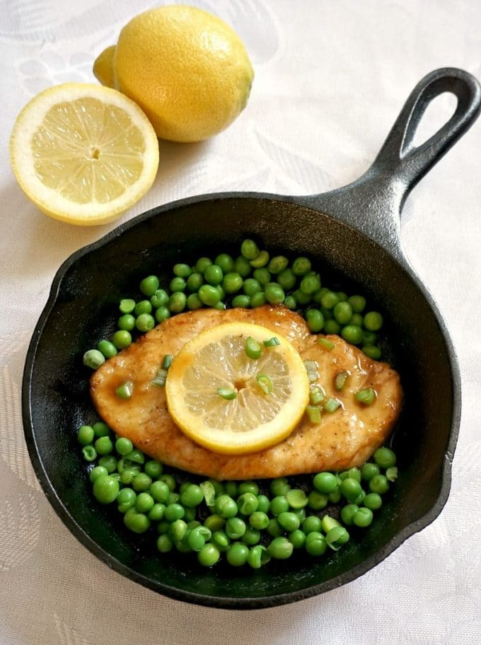 Overhead shot of a iron cast skillet with a chicken breast topped with a lemon slice and peas around, a lemon and a lemon slice at the top of the skillet