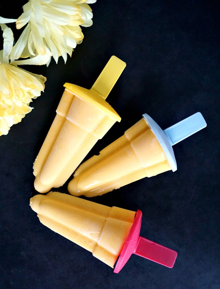 Overhead shot of 3 3 mango lassi popsicles with 2 flowers next to them
