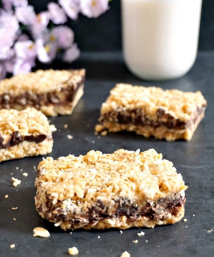 4 no-bake chocolate oat bars on a black table cloth with flowers and a glass of milk in the background