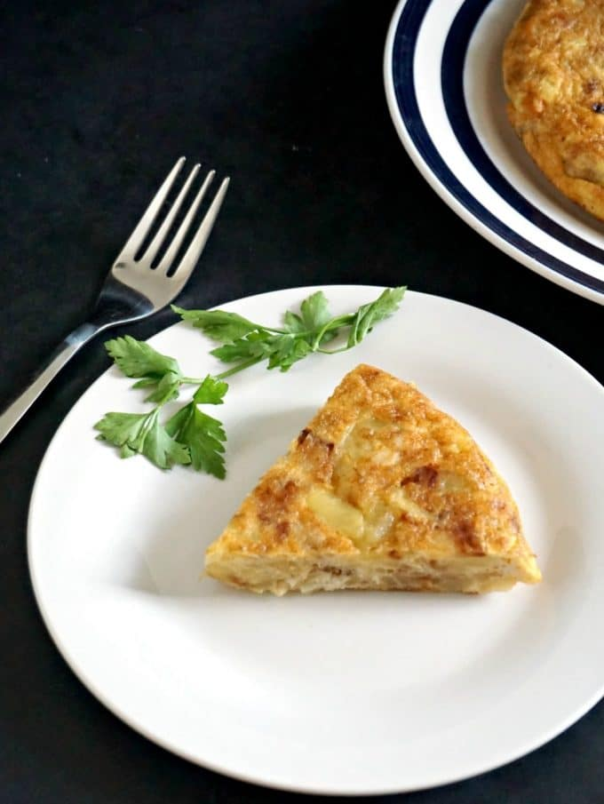 A white plate with a slice of Authentic Spanish Tortilla and a parsley sprig, and a fork next to the plate