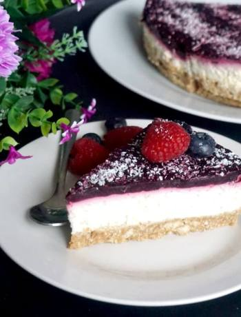 A slice of coconut cheesecake on a white plate with a teaspoon next to it, another white plate with cheesecake in the background
