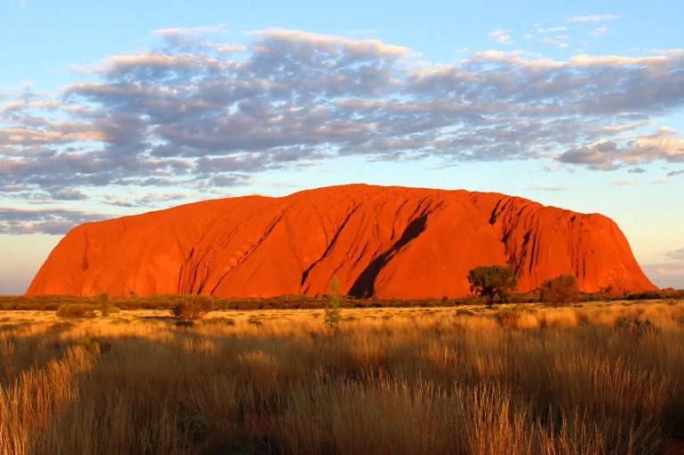 Bei Sonnenuntergang erstrahlt der Uluru in leuchtendem Rot