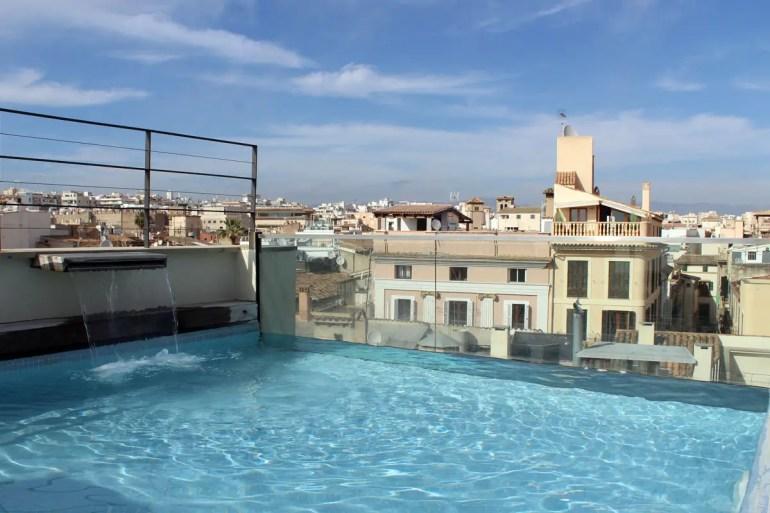 Pool mit Ausblick über die Dächer der Stadt im Hotel Tres