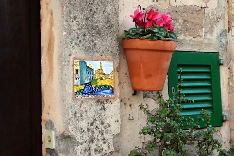 Die Keramikschilder neben den Haustüren Keramik-Schilder neben den Haustüren erzählen Legenden von der Inselheiligen Catalina Tomàs
