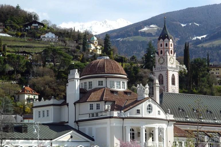 Meran: Hinter Kurhaus und Stadtpfarrkirche öffnet sich der Blick auf die Berge