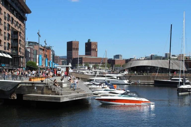 Vom Hafenviertel Aker Brygge aus hast du einen Blick über den Hafen bis zum Rathaus