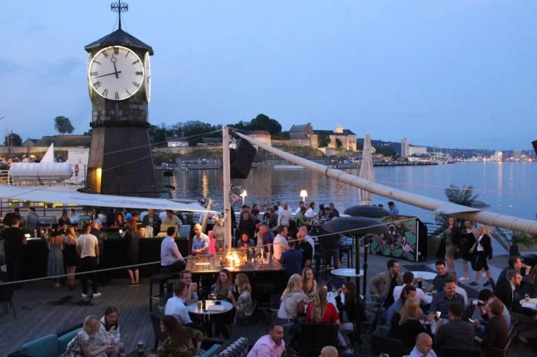 In den Bars von Aker Brygge kannst du abends auf den Hafen schauen