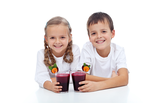 Happy smiling kids with fresh squeezed red vegetabless juice