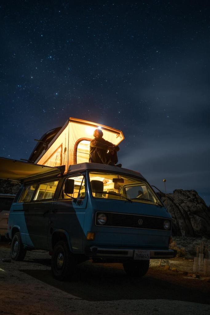 vanlife vivre dans un van nuit van éclairé homme sur le toit