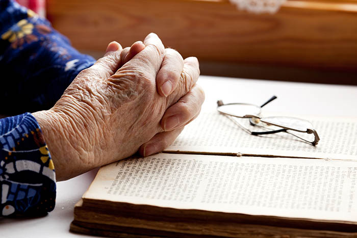An old pair of hands in prayer on a book