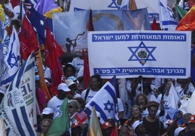 Evangelical Christians from around the world wave their national flags along with Israeli flags as they march in a parade in Jerusalem to mark the Feast of Tabernacles .