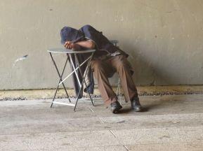 Homeless man naps as tourists pass.