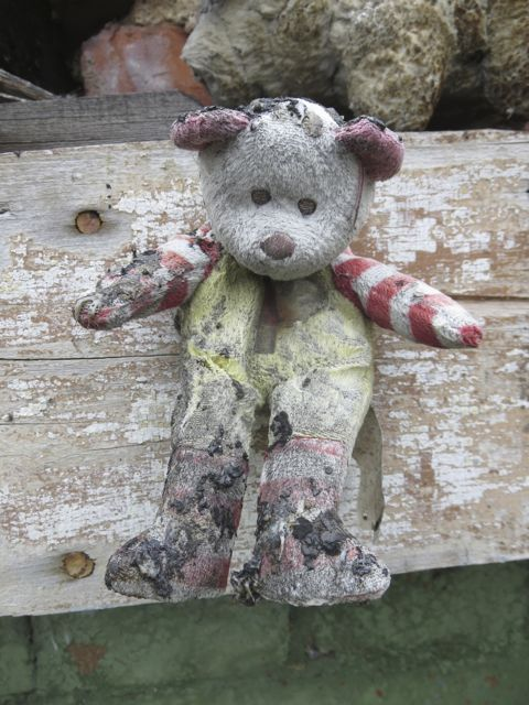 Teddy bear pinned to wreckage of burnt home.