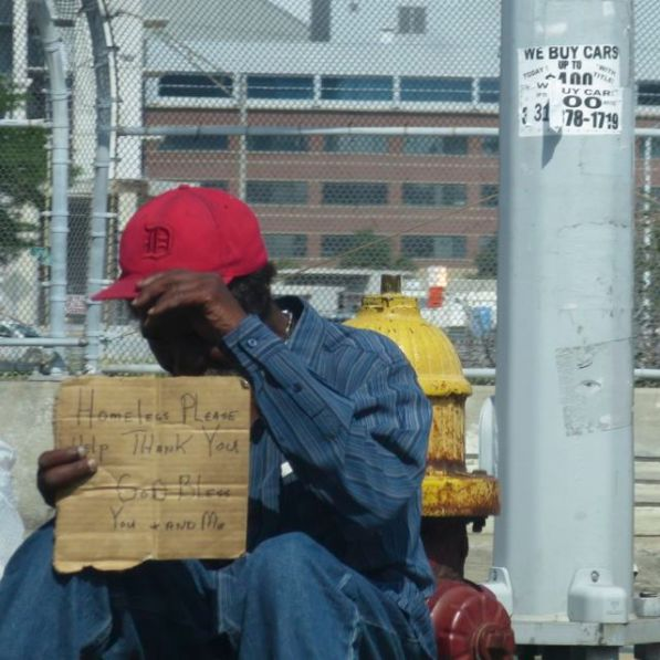 Homeless shields himself from camera's stare.