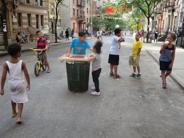 Jeo (in blue) plays checkers on a garbage can at 159th Street
