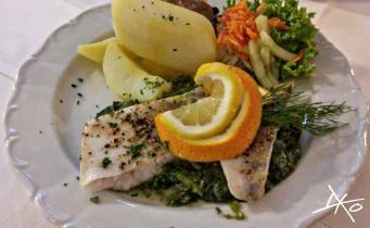 Teller mit Fisch auf Spinat und Kartoffeln