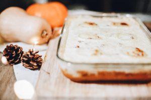 un plat avec un gratin de courge butternut avec une décoration pomme de pin et courges