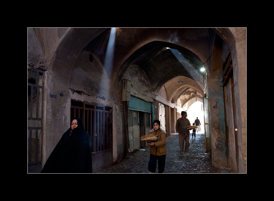 People buying naan bread on one of the streets in the old part of Yazd city, Iran.