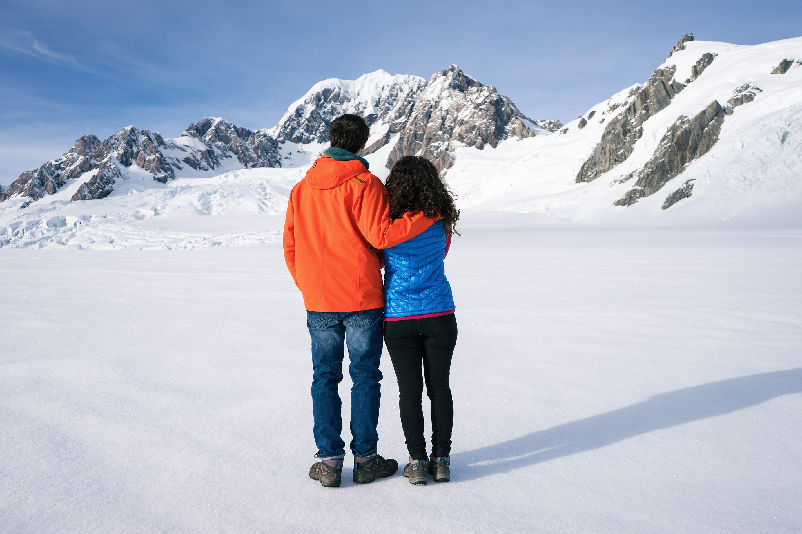 Southern Alps From Above Glacier Landing Couple Standing In Front Of Mountains