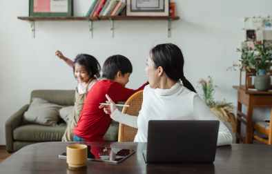young ethnic woman trying to work at home with active children