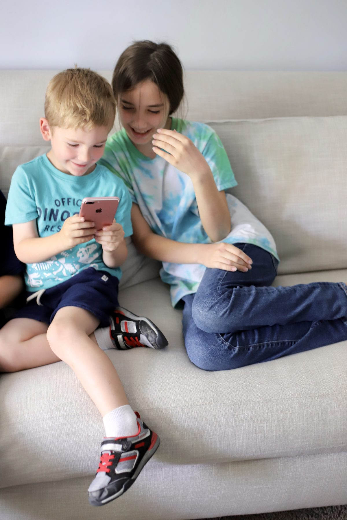 Kids playing on an iphone.