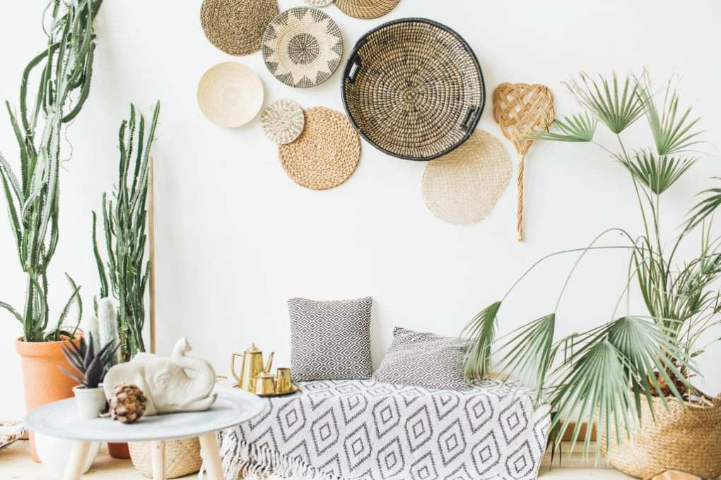 Modern minimal home interior design. Pillows, golden teapot, decorative straw plates, Scandinavian blanket, tropical palm tree, succulent and decorations.