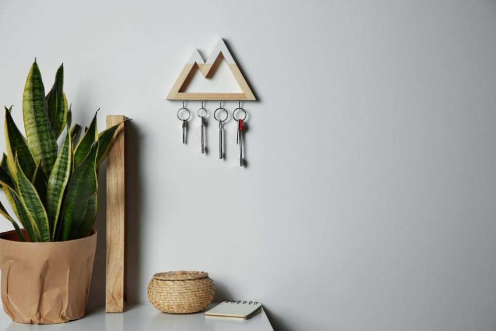 Wooden key holder on light wall indoors. Space for text