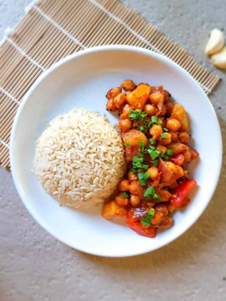 Sweet and sour chickpeas serve with some brown rice in a white plate
