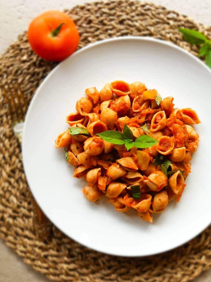 Tomato pasta served on a white plate